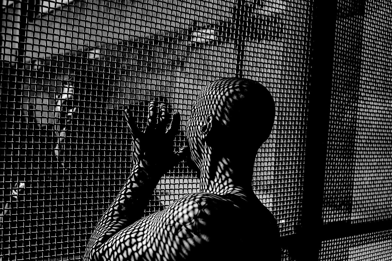 homme en prison devant une grille