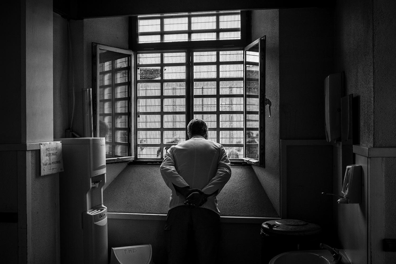 homme en prison devant une fenêtre
