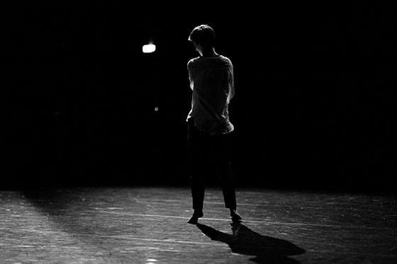 affiche expositions Solo(s), un danseur sur scène du théâtre le Quai à Angers de dos en contre-our