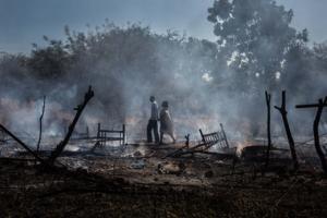 Affiche Expositions Tensions, Photo de Camille Delage d'un couple debout au milieu de leur village en cendres.