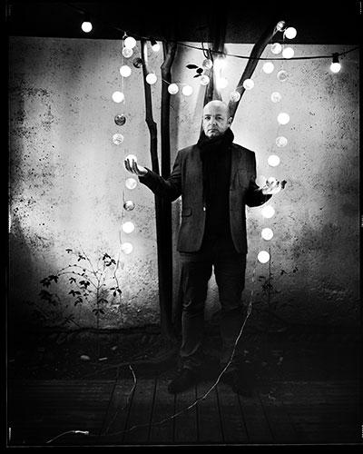portrait Philippe Guionie noir et blanc tenant une guirlande lumineuse