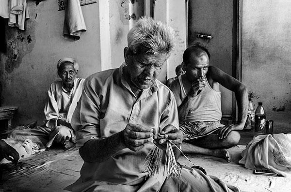 Photographie de Taha Ahmad d'hommes entrain de broder des tissus dans le cadre du festival Photographique Influences indiennes à Beaucouzé