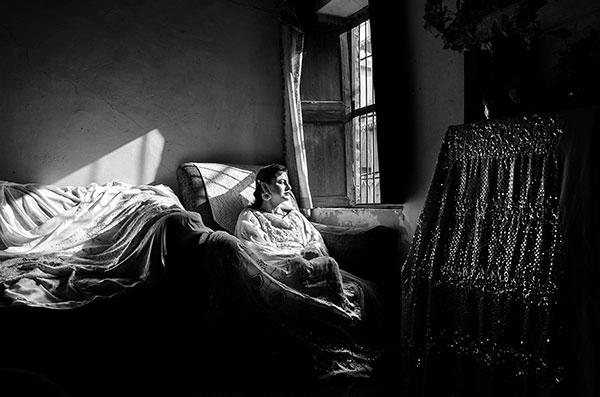 Photographie de Taha Ahmad d'une femme assise devant une fenêtre dans le cadre du festival Photographique Influences indiennes à Beaucouzé