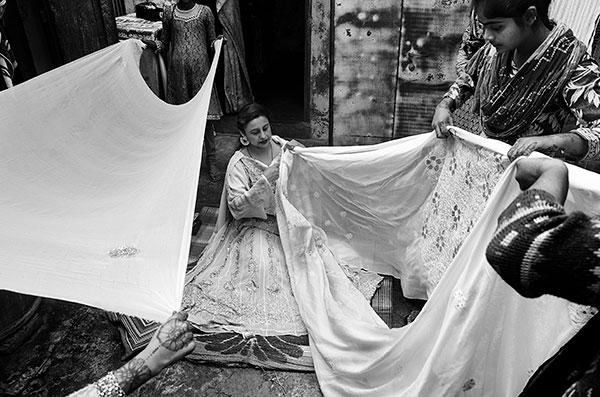 Photographie de Taha Ahmad de femmes pliant des tissus brodés dans le cadre du festival Photographique Influences indiennes à Beaucouzé