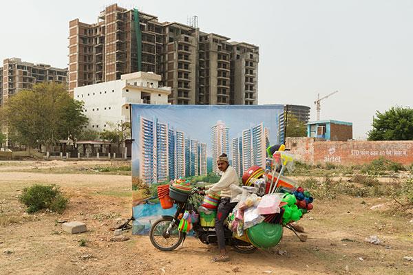 Photo d'Arthur Crestani d'un homme à moto devant un immeuble en Inde dans le cadre du festival Photographique Influences indiennes à Beaucouzé