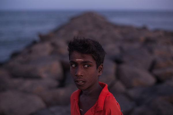 Photo de Karine Dias d'un enfant indien devant une jeté en pierres devant la mer dans le cadre du festival Photographique Influences indiennes à Beaucouzé