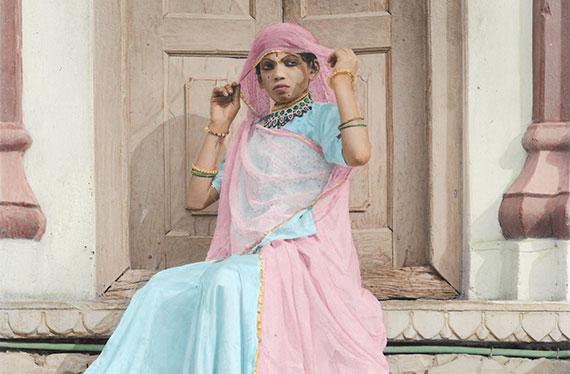 Photographies de Vasantha Yogananthan d'une jeune homme en sari rose et bleu assis sur des marches